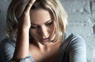 Eine Frau zeigt Symptome von Angst und fasst sich an den Kopf