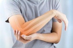 Mensch hält schmerzenden Arm.