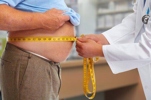 Arzt misst den Bauchumfang eines Patienten