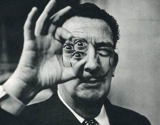 Salvador Dalí hält in seiner Hand drei Augen