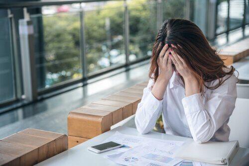 Besorgte Frau, die auf der Arbeit von Angst gequält wird
