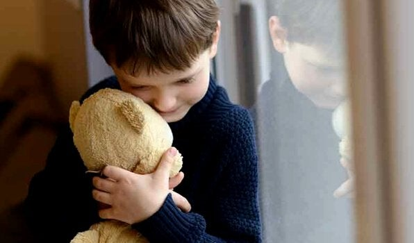 Knabe kuschelt mit Teddybär