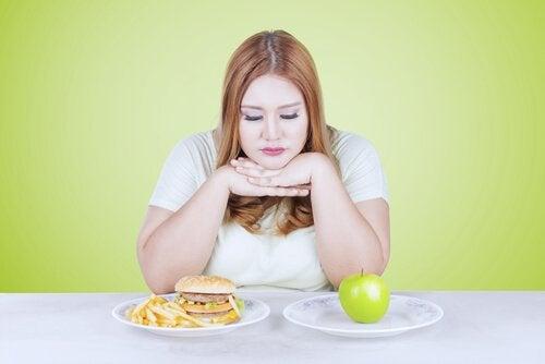 Eine Frau kann sich nicht entscheiden, ob sie lieber den Apfel oder den Burger essen soll