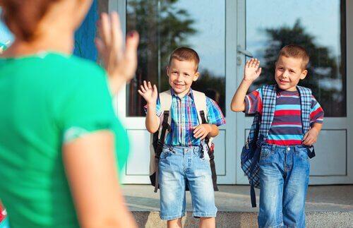 Brüder verabschieden sich von ihrer Mutter für ihren ersten Schultag