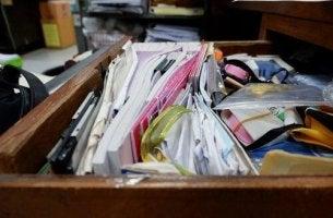 Messie-Syndrom - Eine Schublade ist vollgestopft mit verschiedenen Dingen, überwiegend Papierkram.