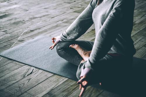 Frau macht Yoga auf einer Matte zu Hause