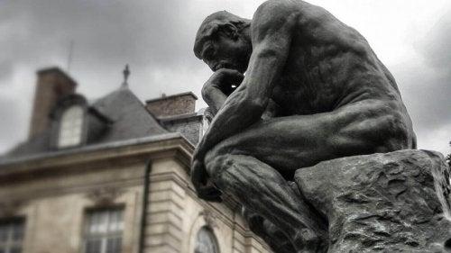Eine Statue eines Menschen in denkender Pose.