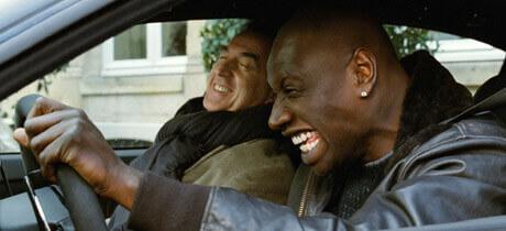 Driss und Philippe sitzen lachend im Auto
