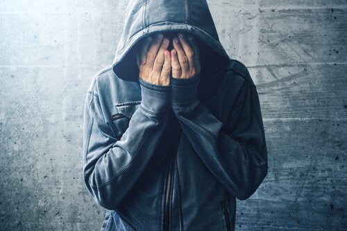 Ein Mann in Kapuzenpulli verdeckt sein Gesicht.