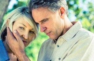 Midlife-Crisis - Ein besorgtes, älteres Paar in der Midlife-Crisis lehnt sich aneinander. Der Mann hält das Gesicht der Frau.