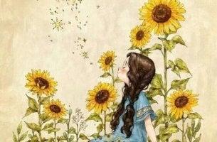 Ein Mädchen genißet den Duft von Sonnenblumen