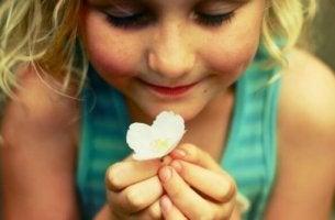 Möglichkeiten zum emotionalen Ausdruck - Ein Mädchen hält eine Blüte in den Händen