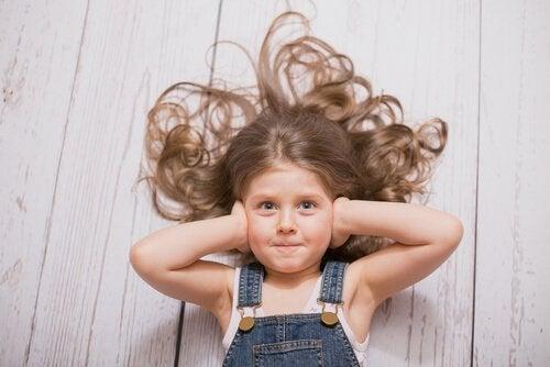 Ein Mädchen, das sich die Ohren zuhält