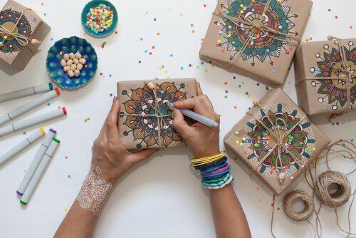 Zwei Hände malen Mandalas auf Geschenke