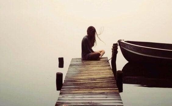 Ein Mädchen sitzt allein an einem Steg