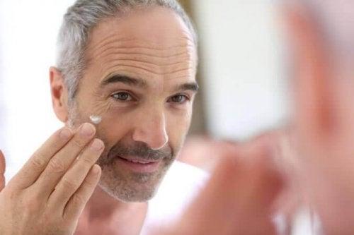 Ein Mann in seiner Midlife-Crisis trägt etwas Creme in sein Gesicht auf.
