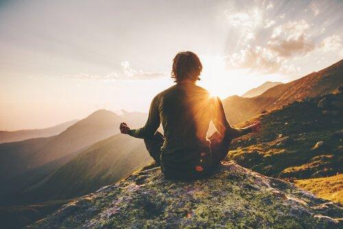 Ein Mann sitzt auf einem Berg in einer Meditationspose.