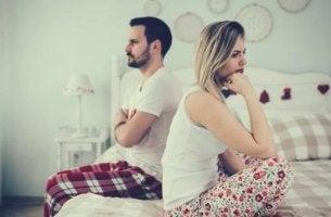 Ein Paar mit Beziehungskrise sitzt Rücken an Rücken auf einem Bett.
