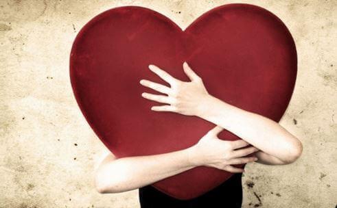 Zwei Arme umarmen ein riesiges Herz aus Stoff