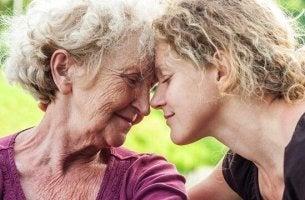 Eine jüngere und ältere Frau lehnen ihre Köpfe aneinander, beide lächeln.