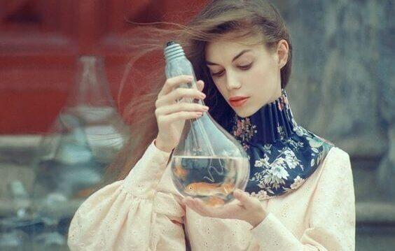 Eine Frau btrachtet eine mit Wasser gefüllte Glühbirne.