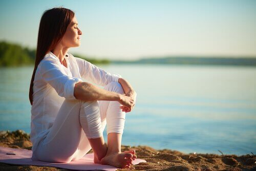 Eine Frau meditiert im Sonnenschein