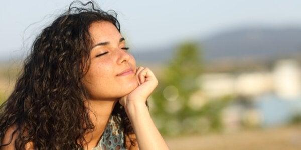 Eine Frau hat die Augen geschlossen und hält ihr Gesicht in die Sonne