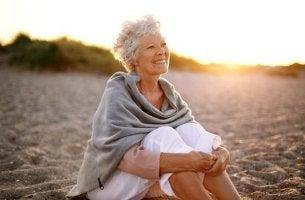 Gesundes Altern - Eine ältere Frau sitzt am Strand.