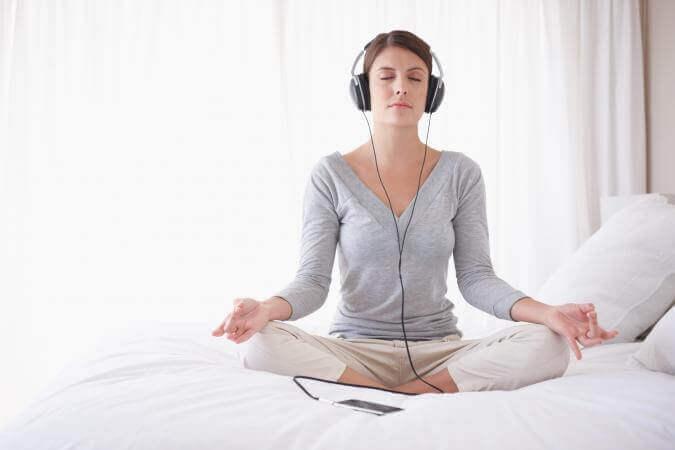 Eine Frau trägt Kopfhörer beim Meditieren im Bett
