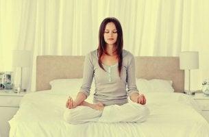 Eine Frau wendet Entspannungstechniken zum Einschlafen im Bett an
