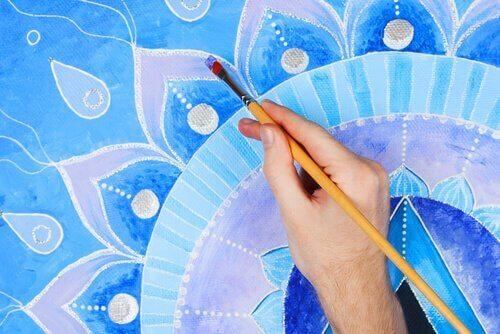 Eine Hand malt ein Mandala in blauen Tönen aus