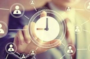Matrix zum Zeitmanagement - Eine Hand tippt auf einem Bildschirm, der eine Uhr anzeigt.