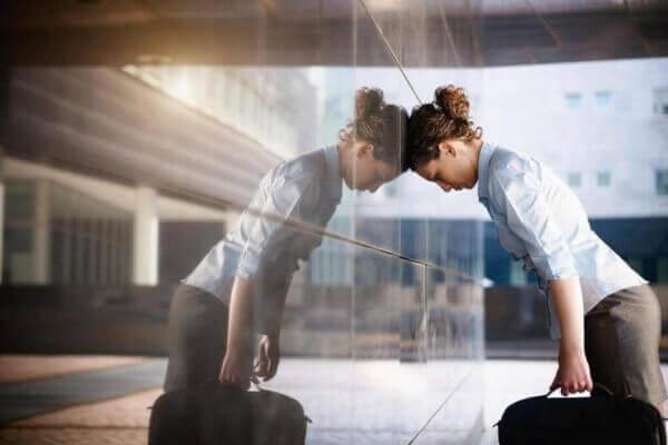 Eine verzweifelte Frau lehnt ihren Kopf gegen eine Glaswand