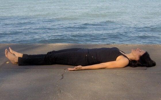 Eine Frau liegt am Meer und wendet Entspannungstechniken zum Einschlafen an