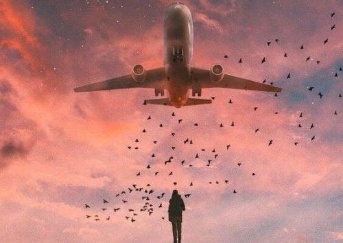 Ein Mann blickt auf ein Flugzeug, das über ihm fliegt.
