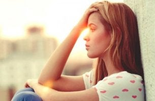 Wenn der Partner Schluss machen will - nachdenkliche Frau sitzt an eine Wand gelehnt
