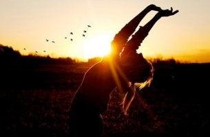 Das menschliche Potenzial - Eine Frau streckt ihre Arme in den Himmel während des Sonnenuntergangs.