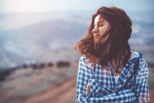 Frau mit geschlossenen Augen steht auf einem Berg.