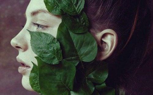 Das Gesicht einer Frau ist bedeckt mit Pflanzenblättern und Apathie.
