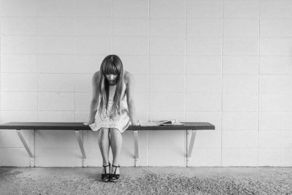 Eine besorgte, junge Frau sitzt auf einer Bank.