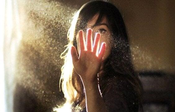 Frau betrachtet ihre Hand im Lichtstrahl