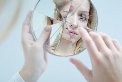 Frau blickt in einen zerbrochenen Spiegel