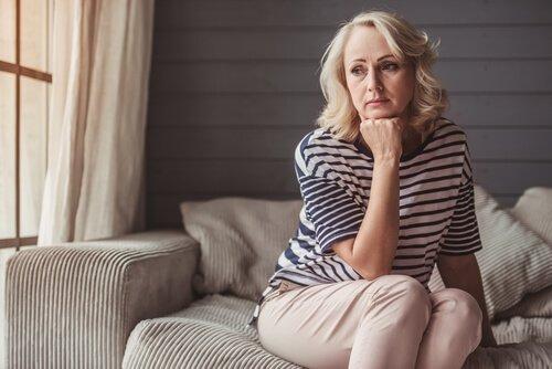 Eine Frau in der Midlife-Crisis sitzt auf einer grauen Couch, ihr Kinn auf ihrer Faust abgestützt und in die Ferne starrend.