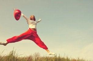 Positive Affirmationen - Frau mit rotem Ballon springt in die Luft