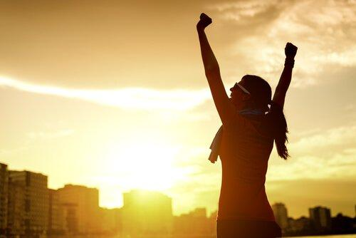 Glückliche und mit Motivation gefüllte Frau, die ihre Arme in die Luft streckt.