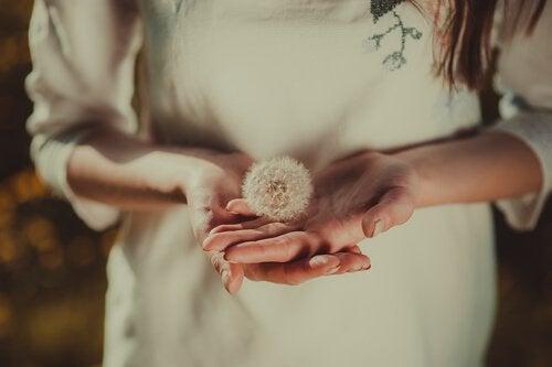 Frau trägt Pusteblume auf der Hand