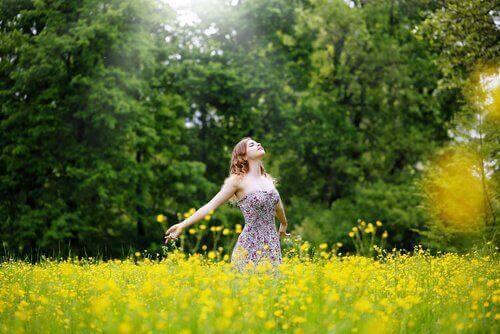 Frau steht im Feld und fühlt sich frei