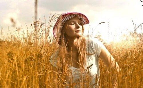 Emotionale Kontrolltechniken - Eine Frau sitzt entspannt in einem Kornfeld.