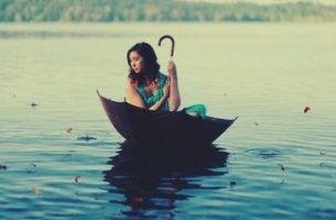 Einen schlechten Tag verbessern - Frau im Regenschirm auf einem See