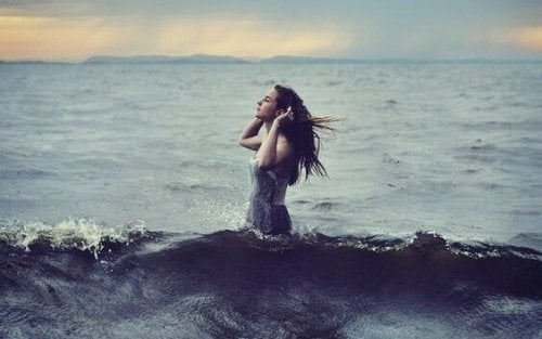 Mädchen lauscht stehend im Wasser.